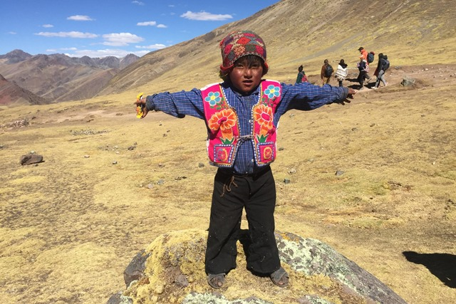 Small boy in bright cultural dress standing in a desert landscape with hands outstretched