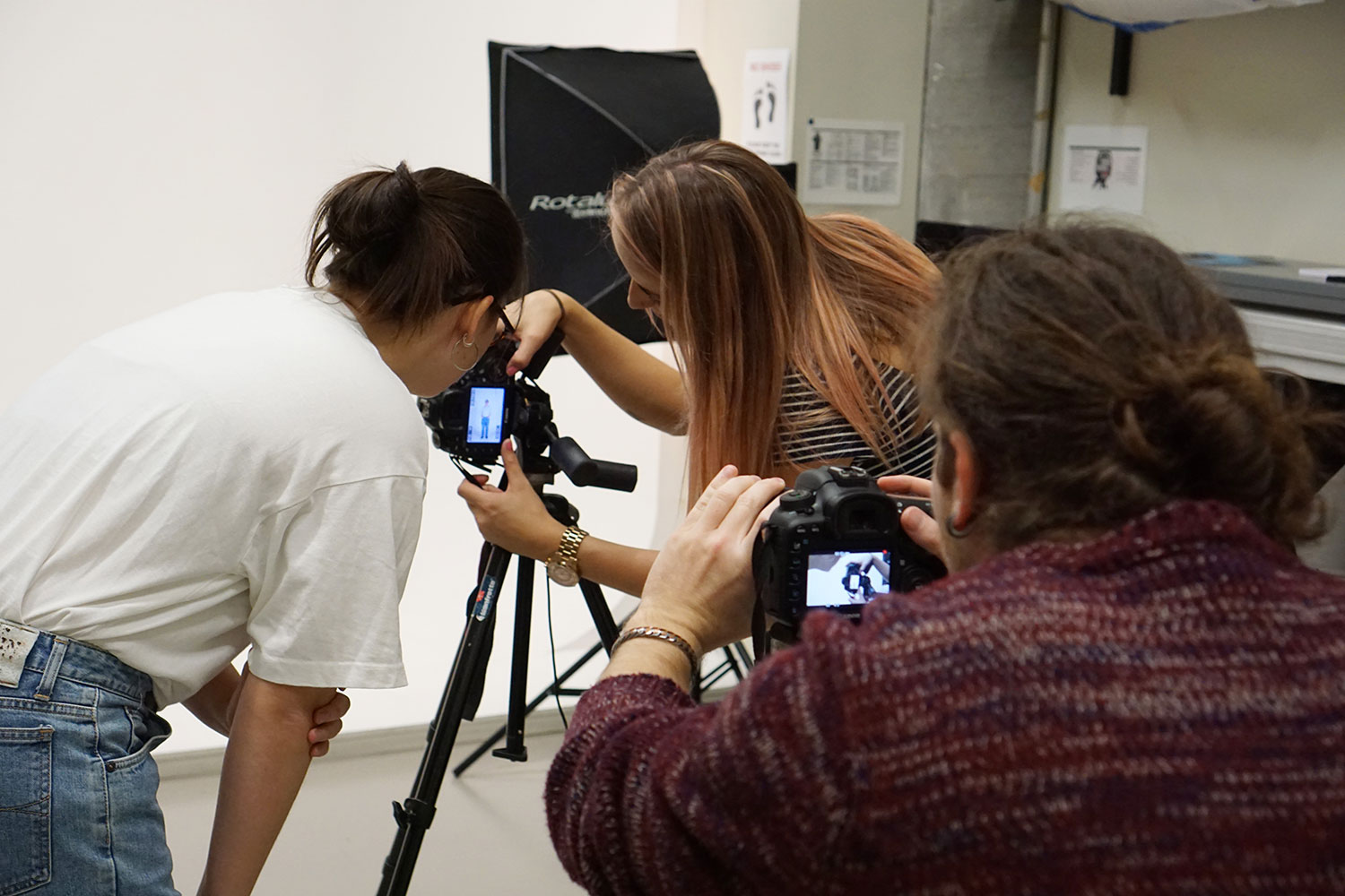 3 people setting up a photo shoot in a photography studio