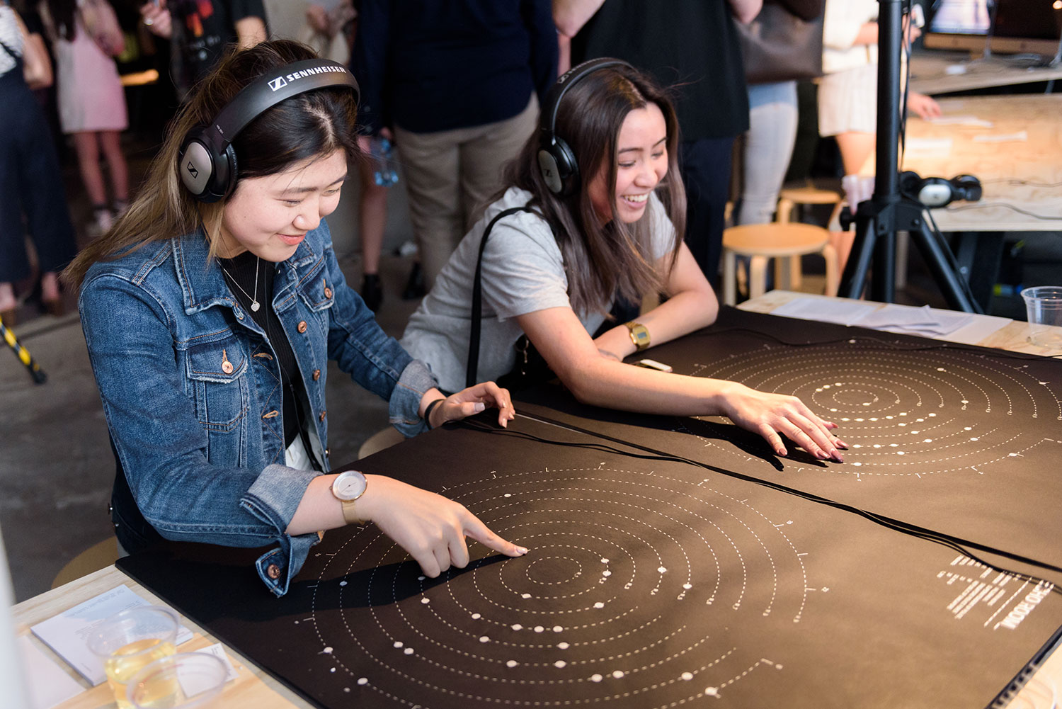 2 woman with headphones enjoy an interactive artwork