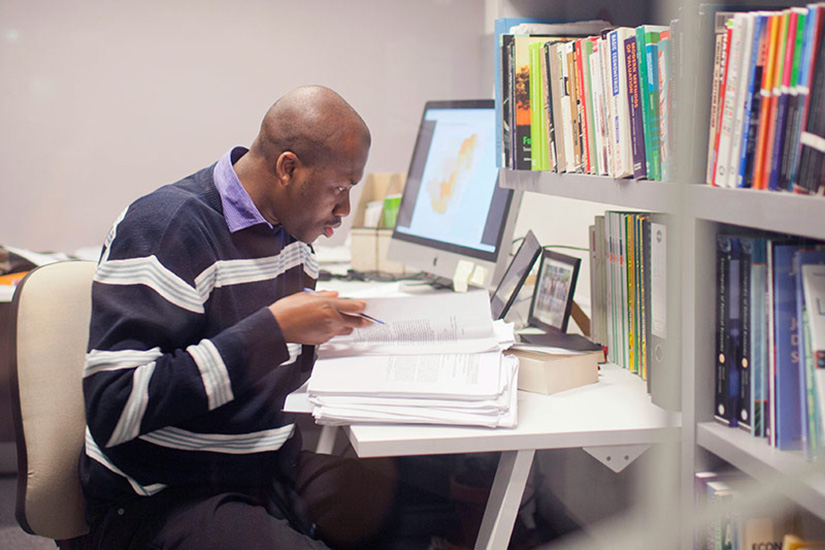 Man sitting at desk with books, computer and written notes