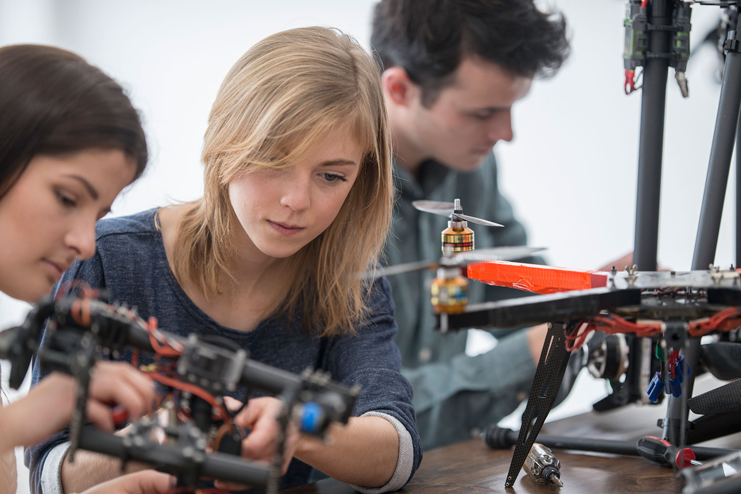 Three students work on drones