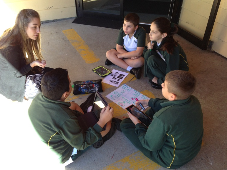 Boys talking to teacher about drama project