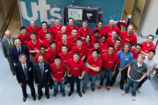 A birds-eye view picture of a groups of CAS members in red UTS:Robotics polo t-shirts.