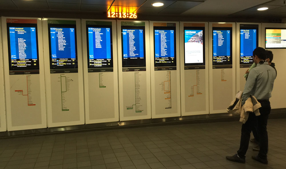 Two people standing in front of train timetable screen boards
