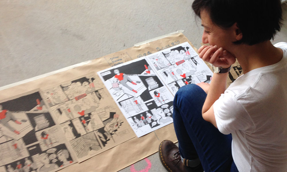 Student looking at zine artwork on studio floor
