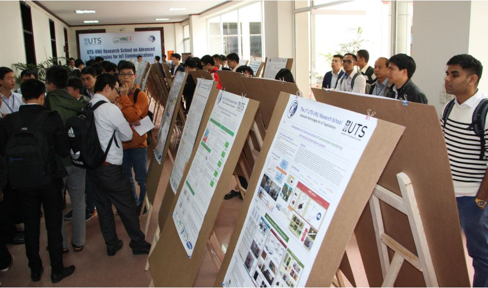 People walk around and study a display of posters on frames running down the centre of a long room.