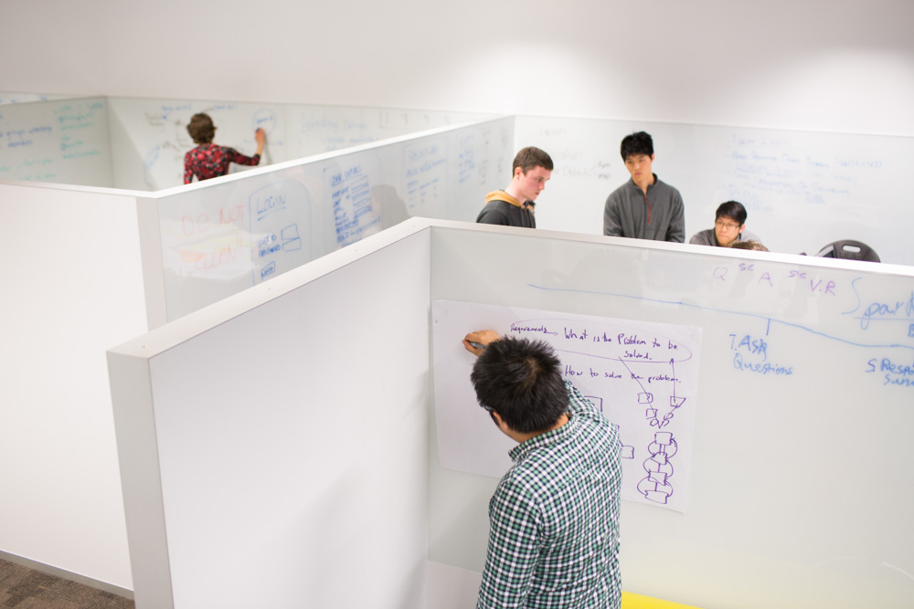 Students write on wall-to-wall white boards in the Software Development Studio to develop ideas