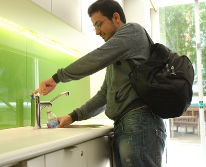 Student filling water bottle in building 5 student lounge