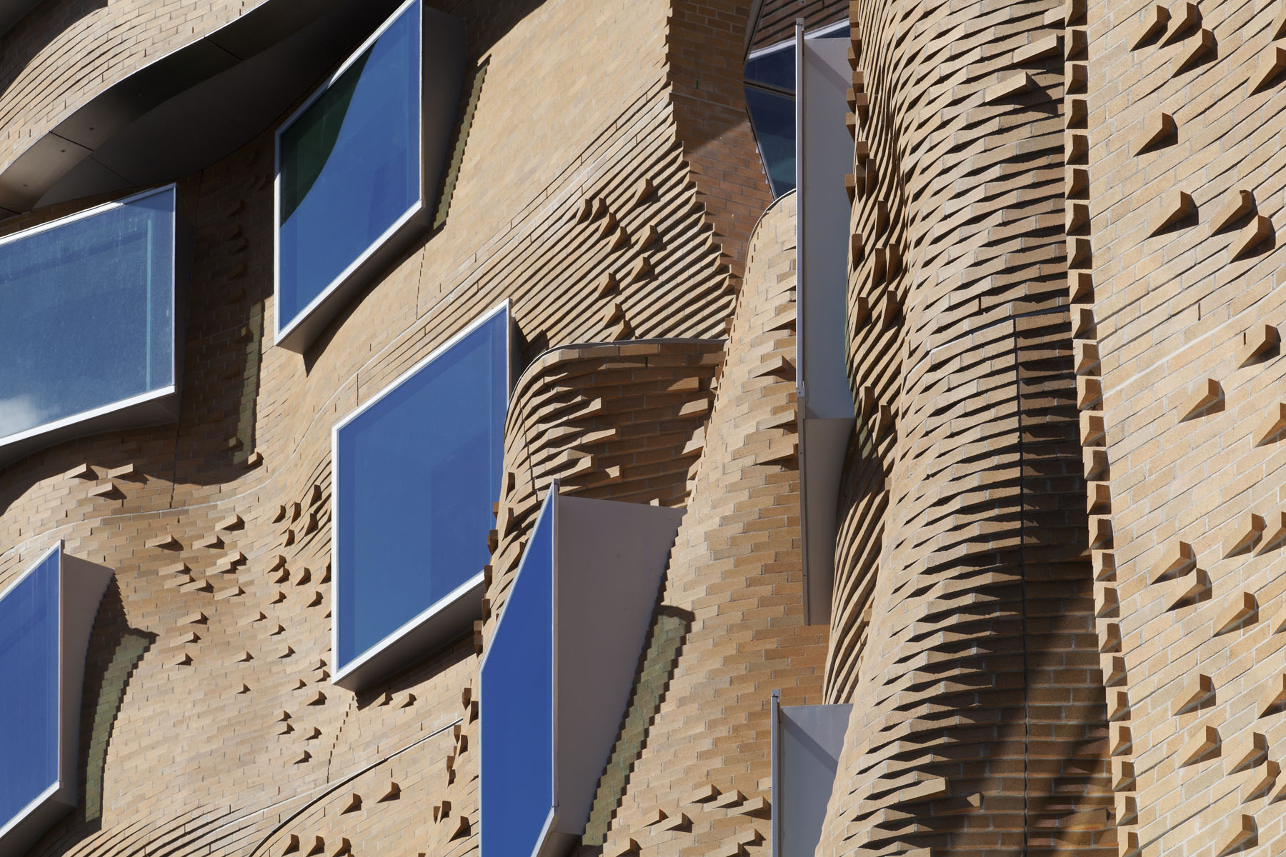 Mary Anne Street - North Canyon. Achieving the fluid appearance of the brickwork proved a technical feat that involved corbelling (stepping) individual bricks to articulate the building's organic shape. The light-coloured bricks – around 320,000 in total