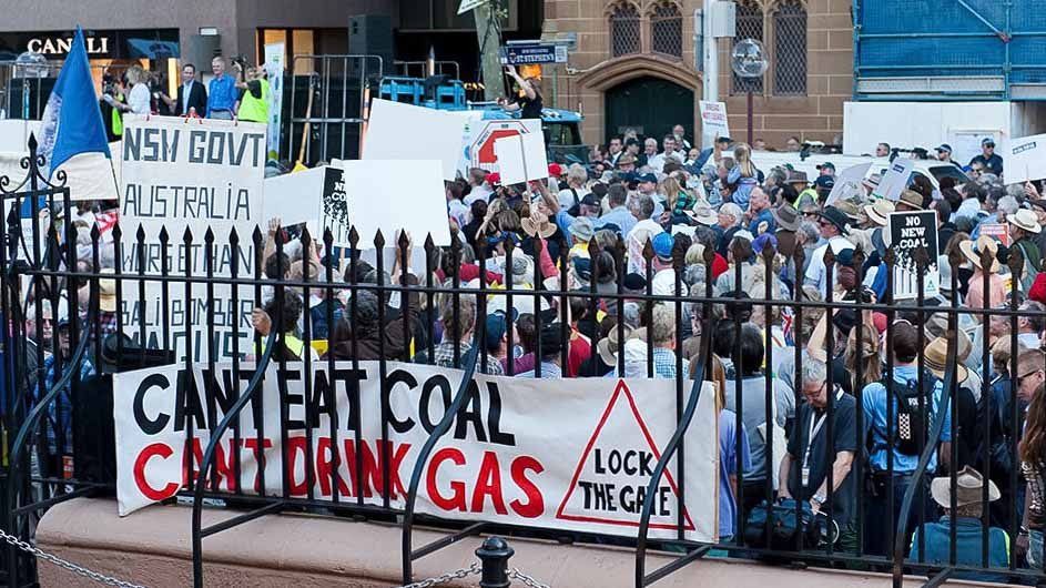 A crowd of people protesting against coal mining