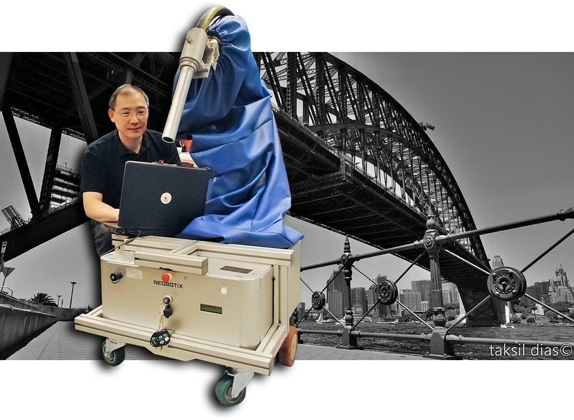 Photo of UTS Professor Kikai Liu and his grit-blasting robot, with the Sydney Harbour Bridge in the background