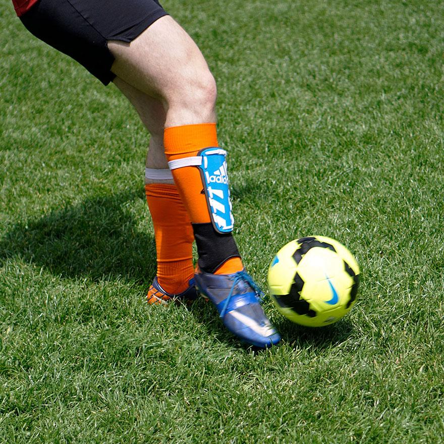 Soccer players legs with a soccer ball on the grass