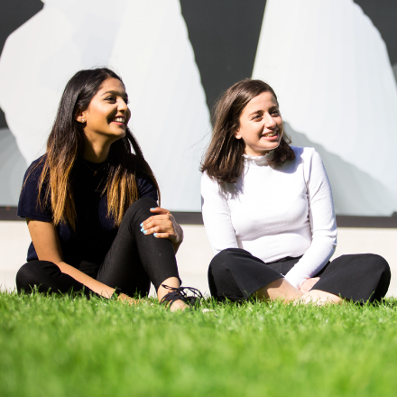 2 woman sitting on grass