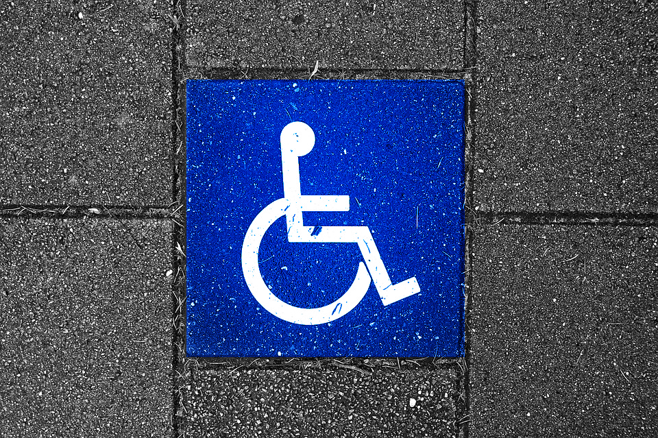 Sign for Person with Disability on pavement
