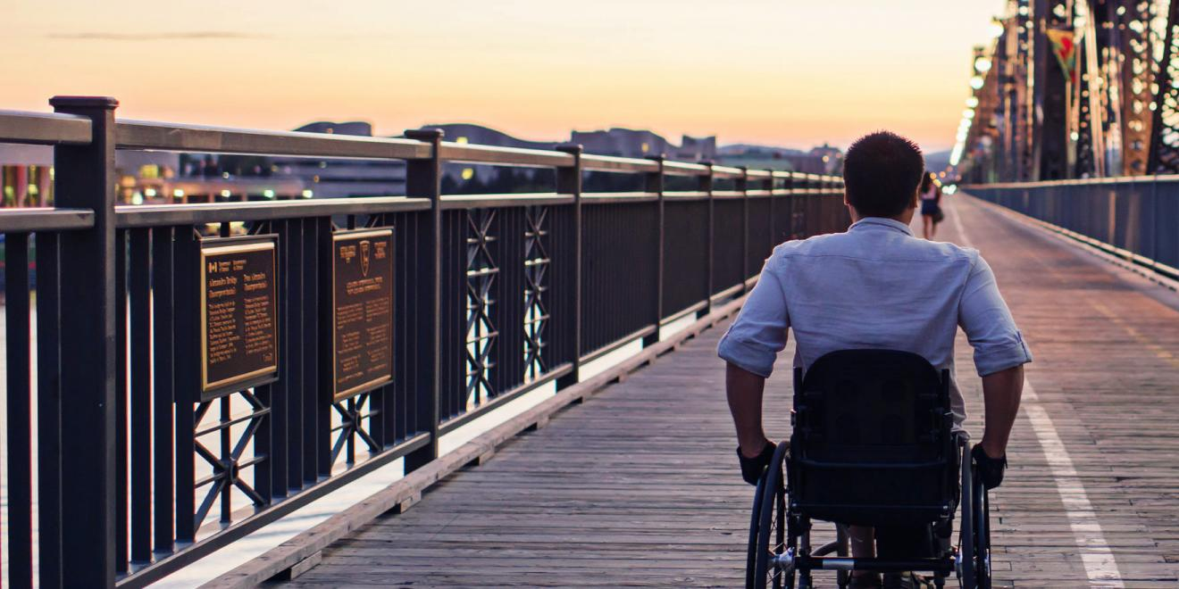 Man on wheelchair moving into the horizon at sunset