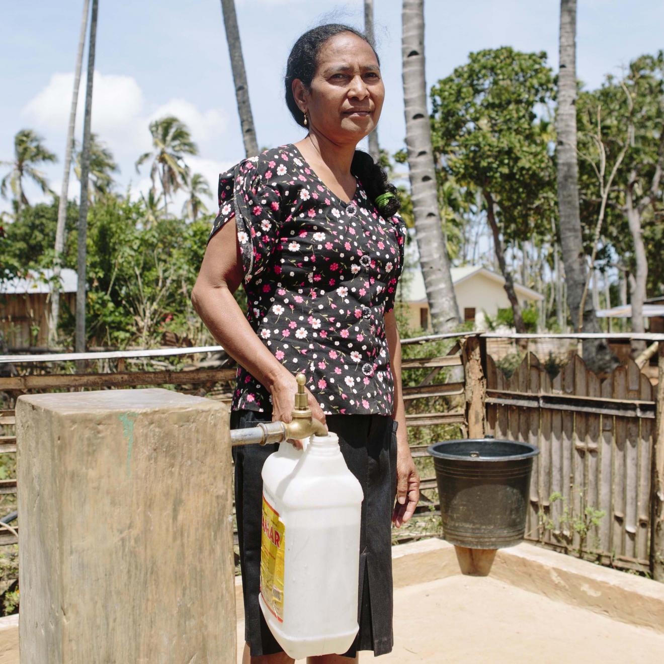 Community member Etelvina holding a water jug at one of the new water points built by WaterAid and partners in Timor-Leste.