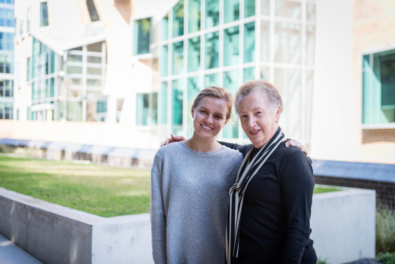 Laurie Cowled and Ellie Slade facing the camera with their arms around each other in front of Building 8