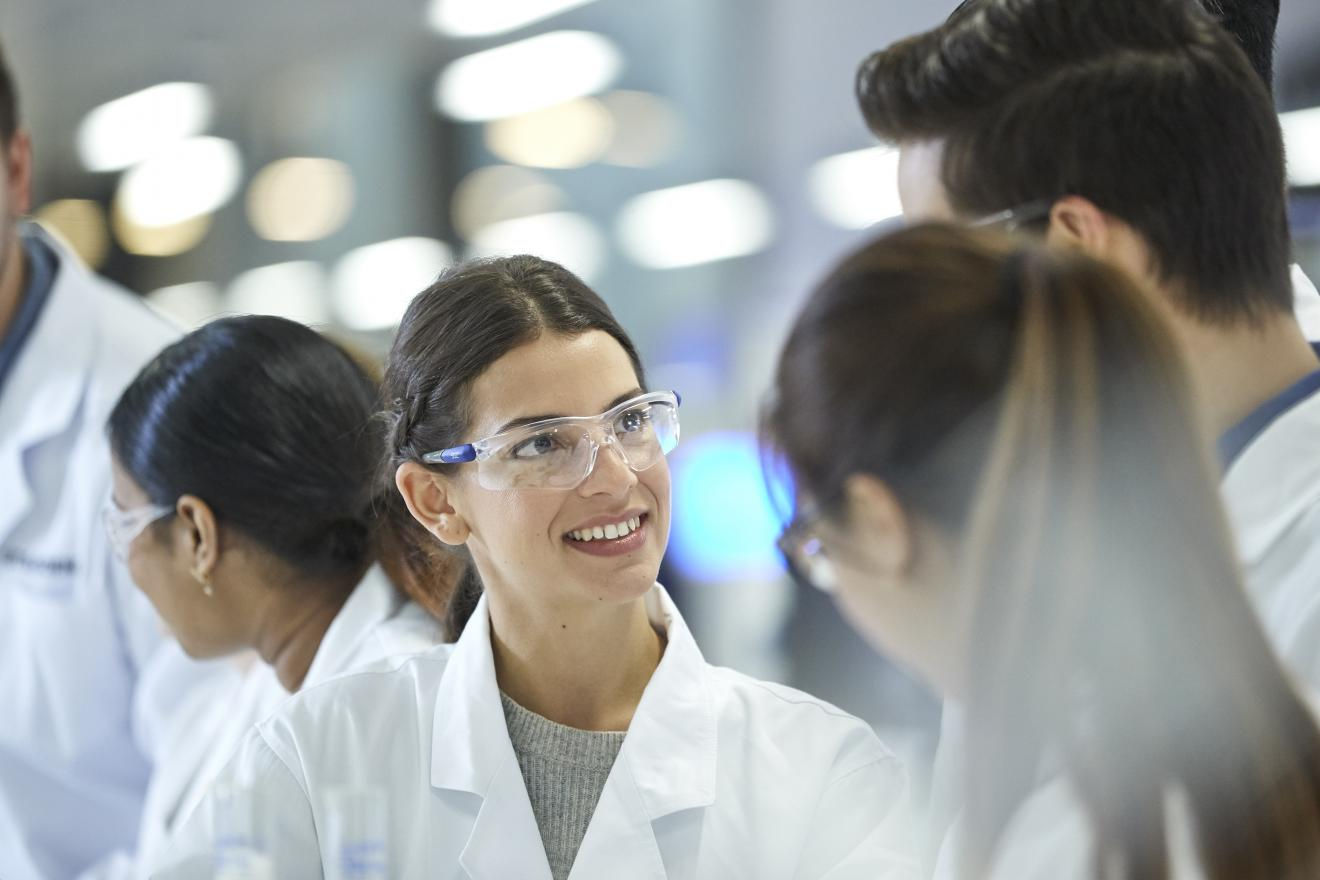 Students in discussion in lab uniforms