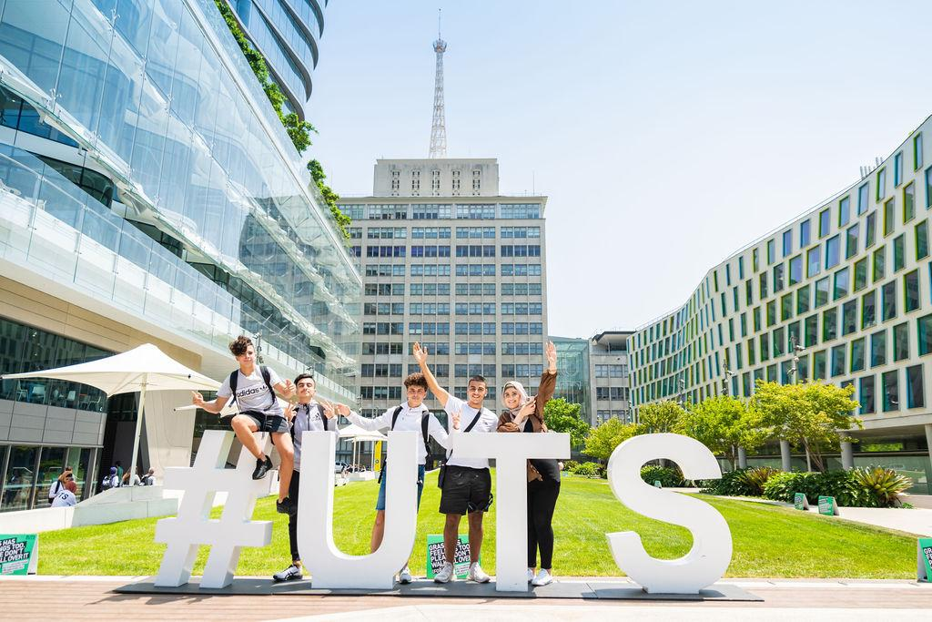 U@Uni Academy students standing in front of giant #UTS letters on the alumni green.