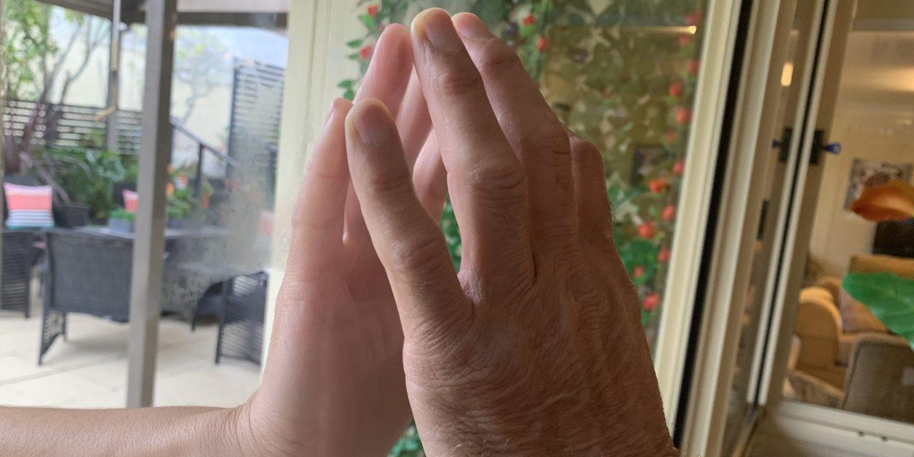 Hands touching either side of a window