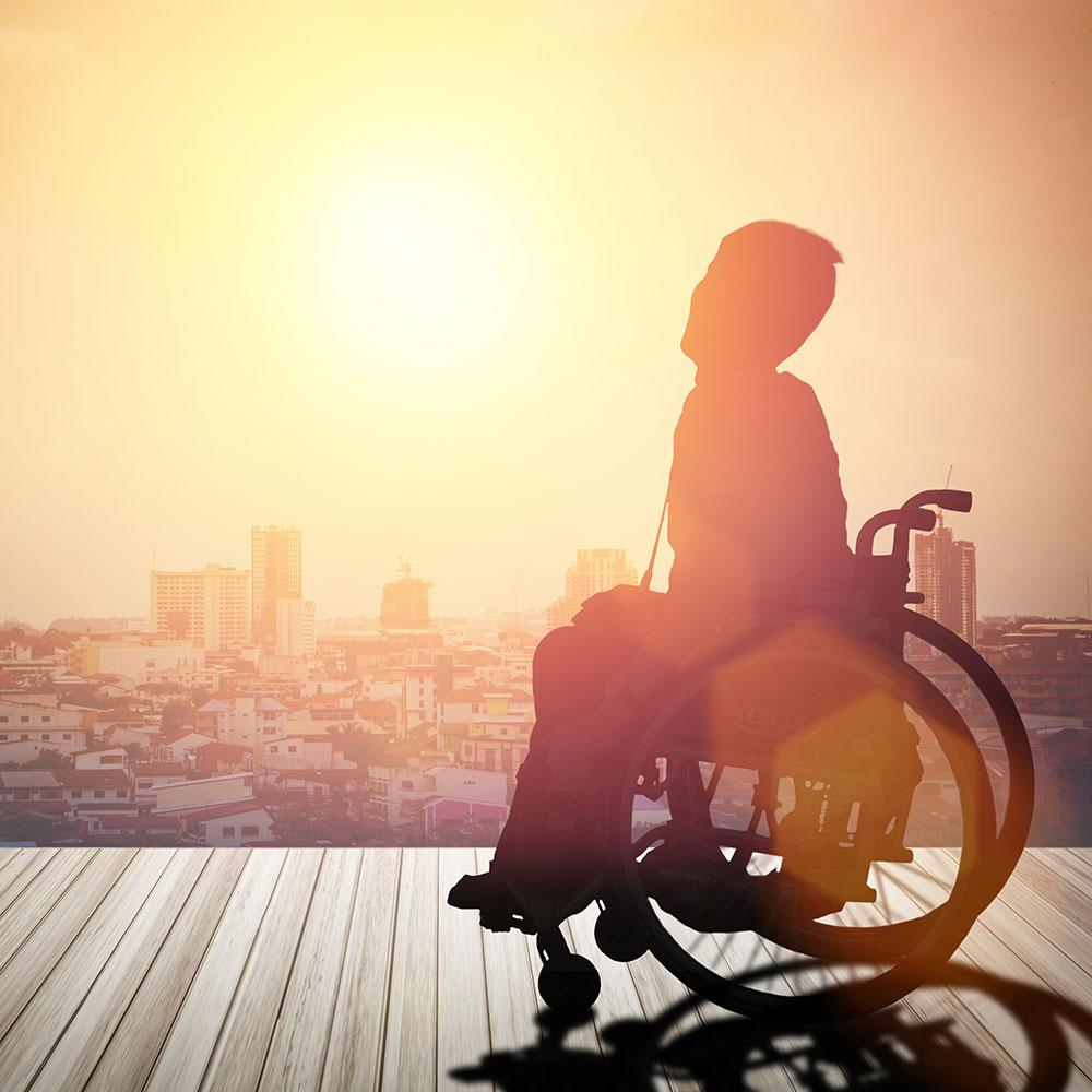 person in wheelchair views sunset over city