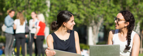 Two female students with laptops on the UTS Alumni green