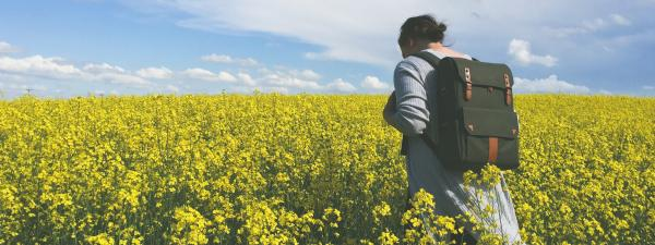 Image of a female student walking through fields with a backpack