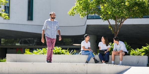 Three students sitting under a tree as a man walks past