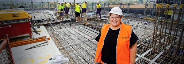 Female smiling on construction site with male workers in background