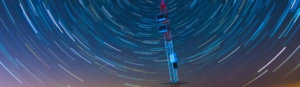 An antenna at dusk with dramatic star trails in the sky above