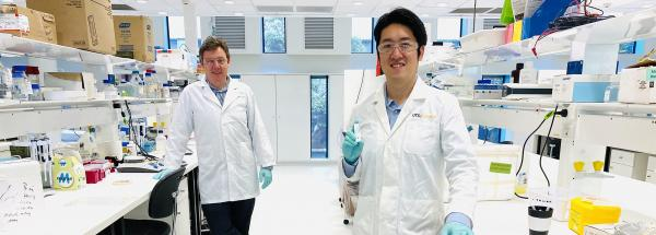 Brian Oliver and Josh Chou standing, socially distanced, in their lab