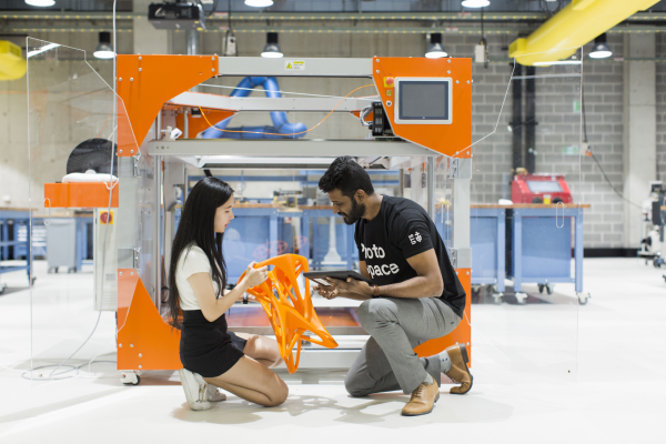 Two students looking at a 3D printed chair inside UTS Protospace