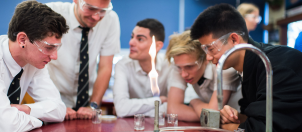 Student in classroom setting with bunsen burner