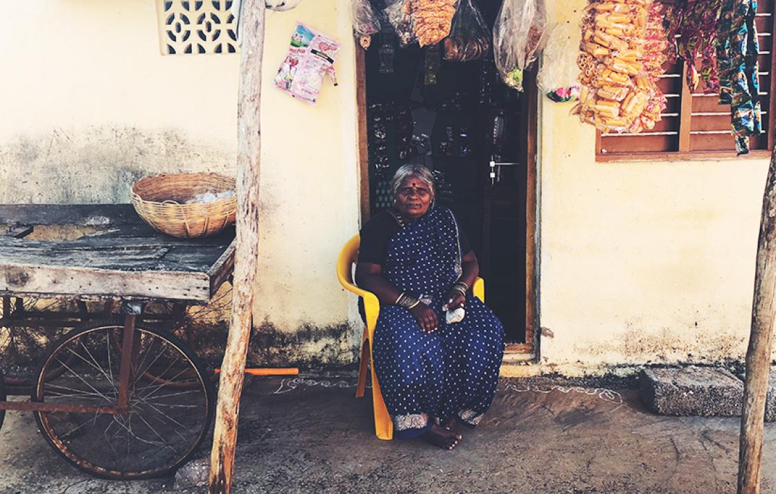 Women on chair sitting outside her shop in Bangalore