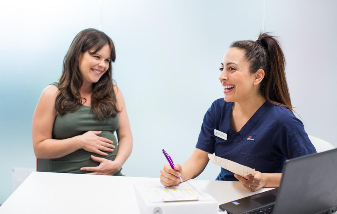 a smiling nurse in front of a laptop with a smiling pregnant woman