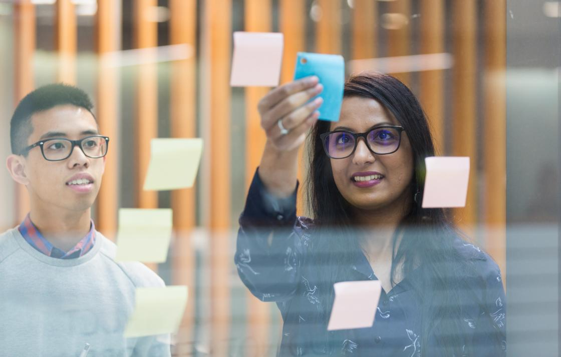 Two students placing paper notes