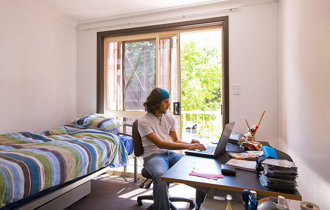 Guy looking at laptop in his room