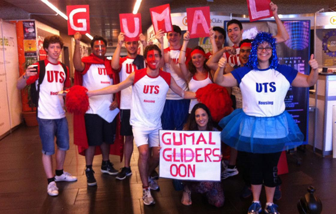 Students dressed up in red, white, blue holding Gumal and Gumal Gliders signs