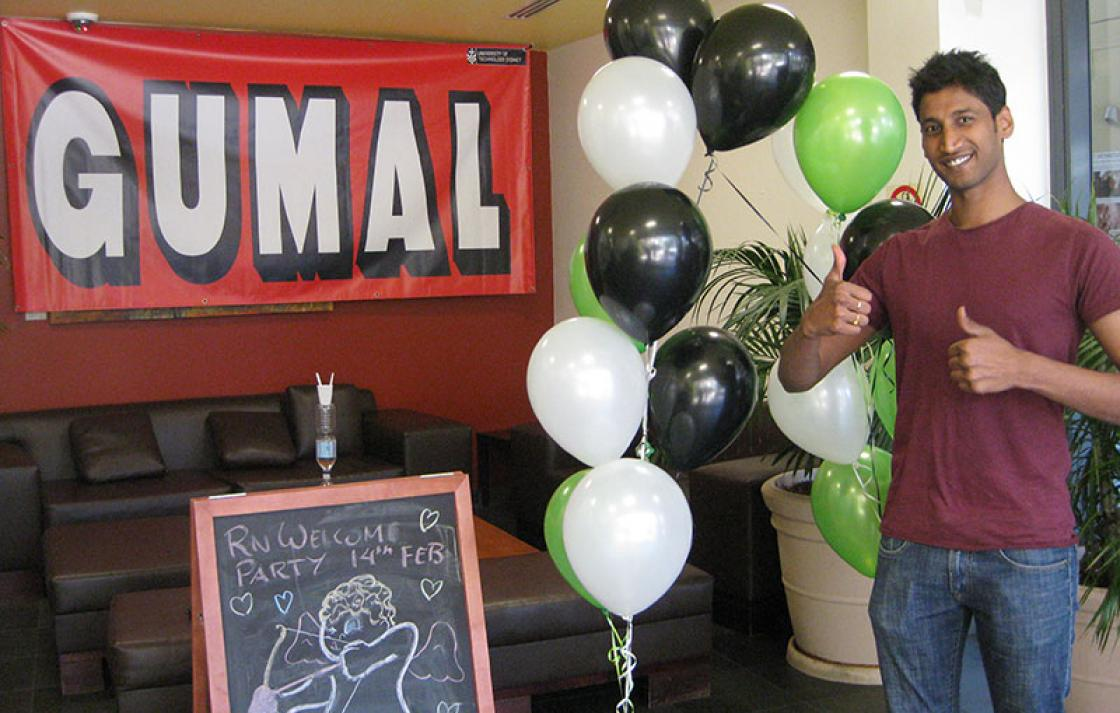Guy giving thumbs up with Gumal sign and balloons in the background