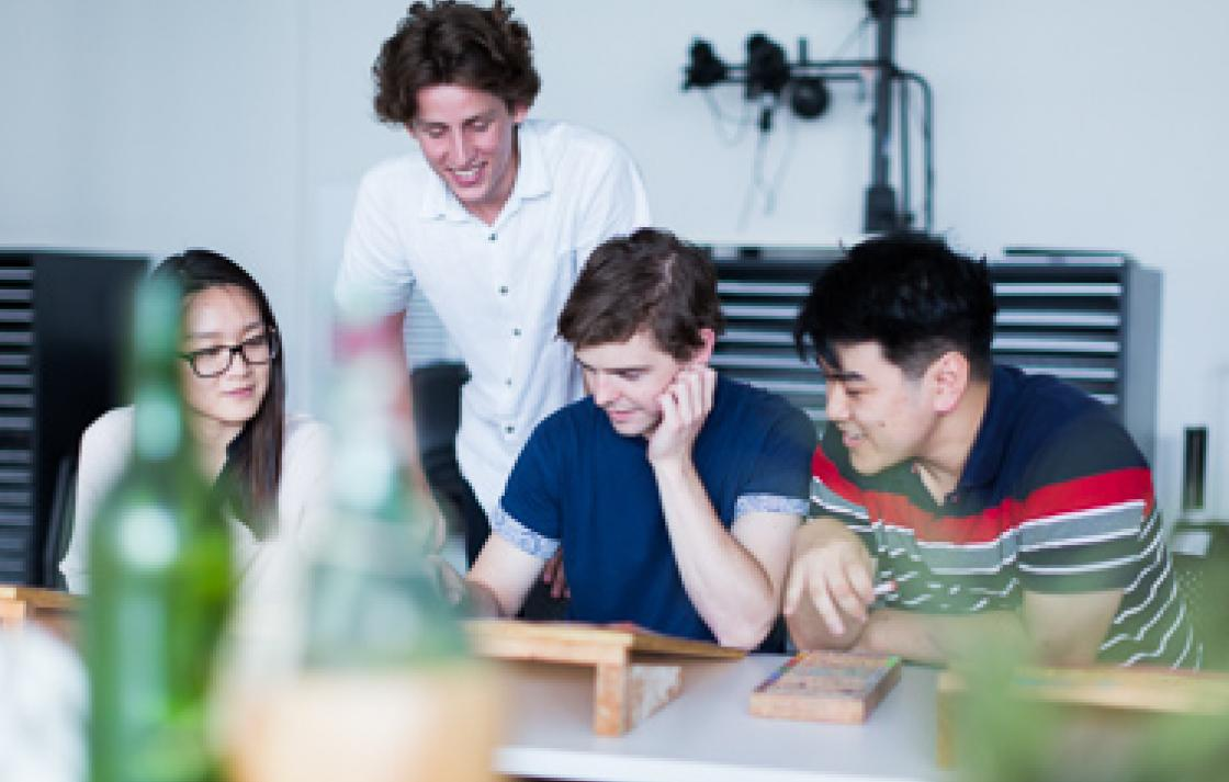 Photo of four students working around a table