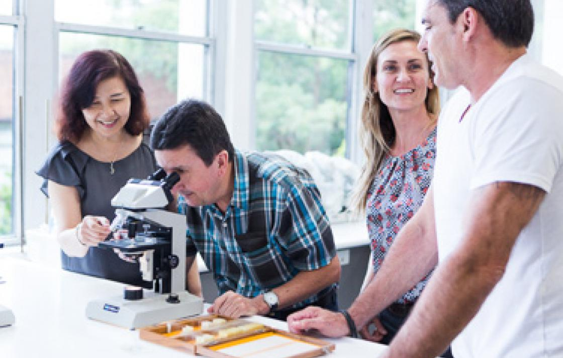 Photo of a man looking into a microscope, with help from a woman. Two other people are in conversation