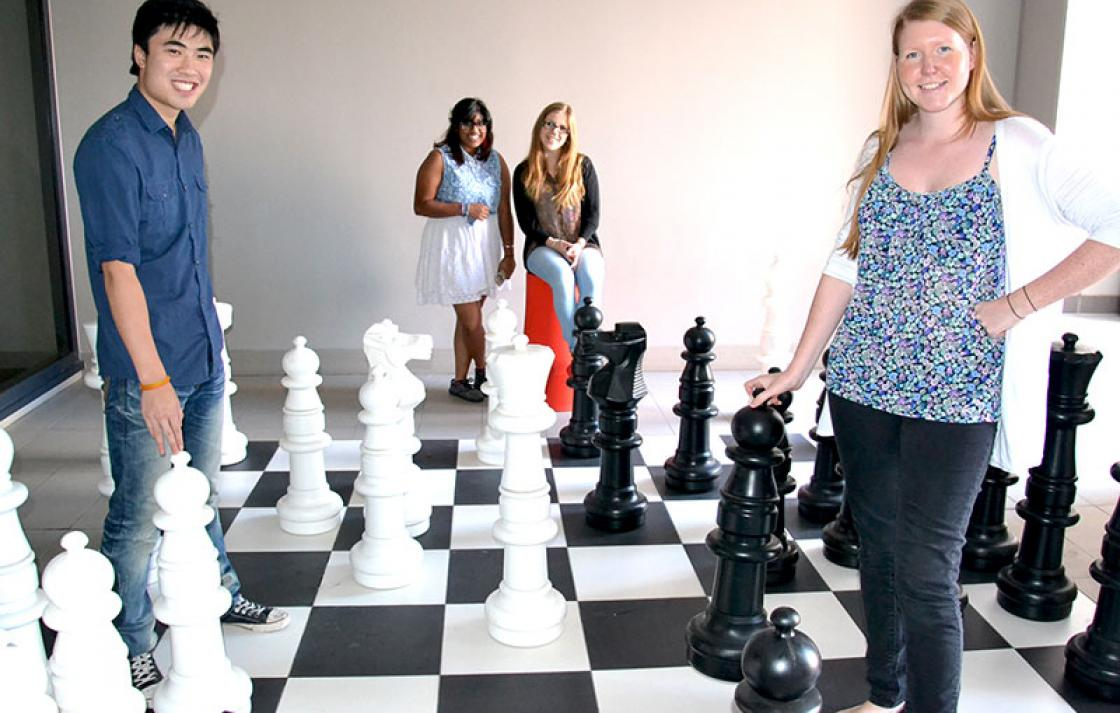 Four people with playing chess