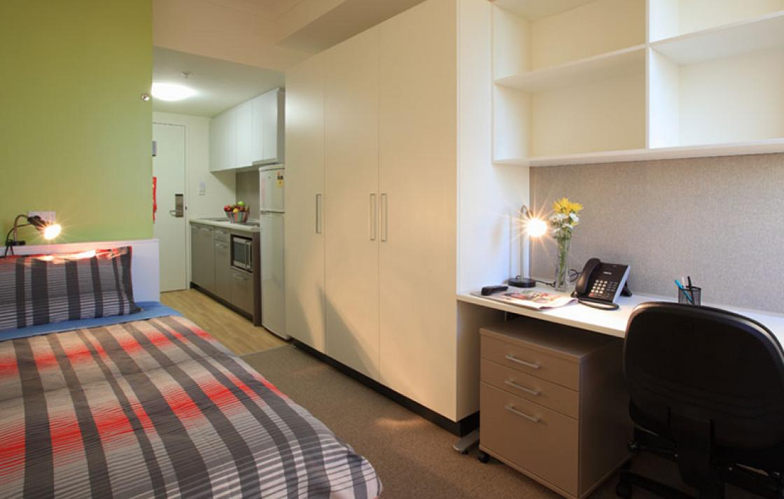 Room with view of bed, kitchen and desk