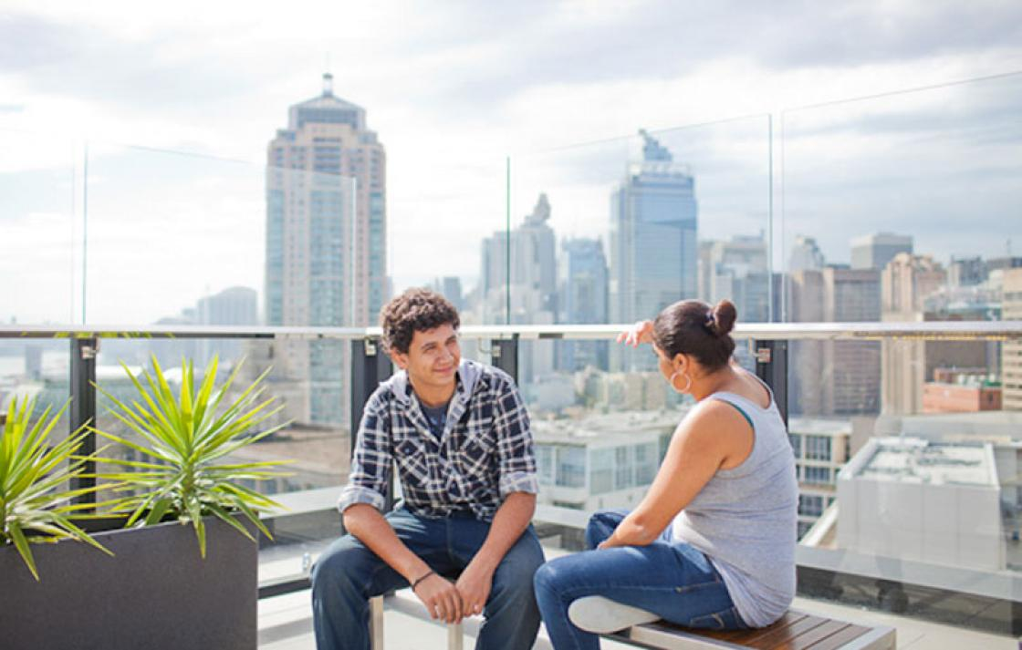 Two people chatting with view of buildings in the background