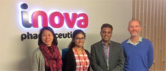 Two females and two males smiling in front of Inova sign.