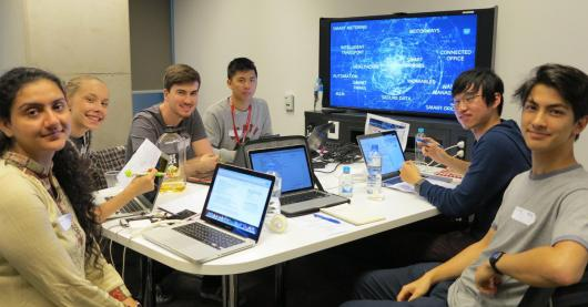 Six students sitting at a table with laptops, they are looking toward the camera. Behind them is a large screen showing a visualisation