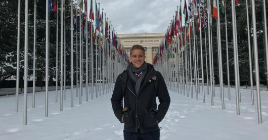 Photo of Nik Dawson standing on snow in front of an avenue of flags at the UN in Geneva
