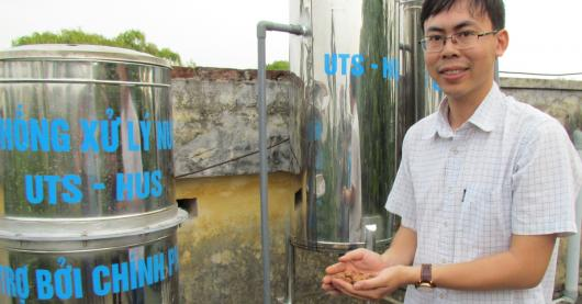 Photo of a man in front of the water filtration system in Vietnam.