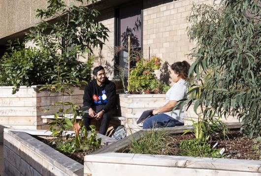 A man and woman sitting in the Waraburra Nura garden, smiling and enjoying the sunshine