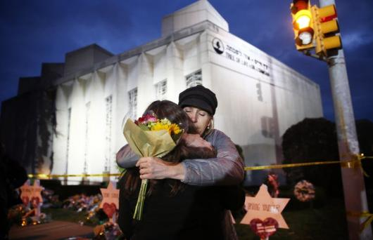 Two women hug before placing flowers at the Star of David memorial in front of the Tree of Life Synagogue